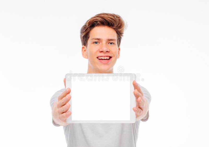 Tableta atractiva de la tenencia del adolescente del estudiante del hombre joven con la pantalla blanca, aislada en el fondo blan fotografía de archivo