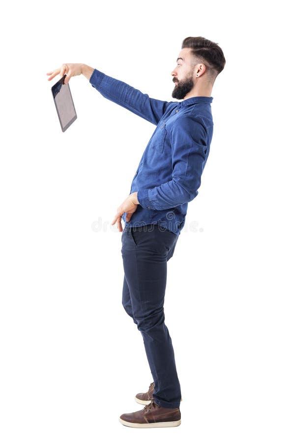 Tableta barbuda chocada de la tenencia del hombre de negocios con dos fingeres Concepto descontentado foto de archivo libre de regalías