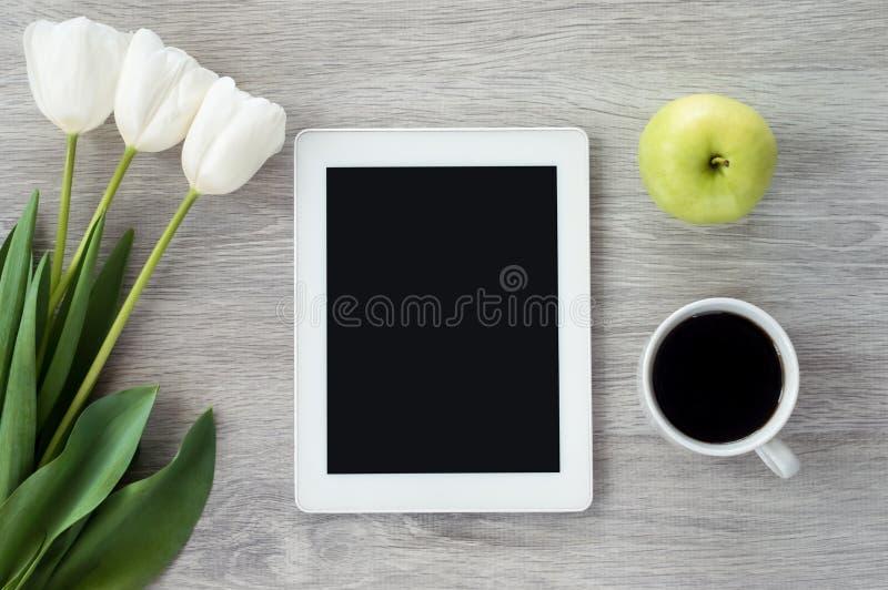 Tableta blanca con las flores blancas, las manzanas verdes y una taza de mentiras del café en una tabla de madera blanca imagen de archivo