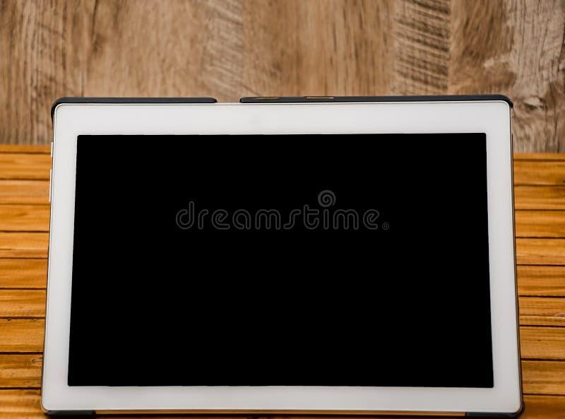 Tableta blanca en fondo de madera imagen de archivo