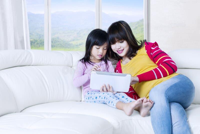 Tableta bonita del uso de la mujer y del niño en casa imágenes de archivo libres de regalías