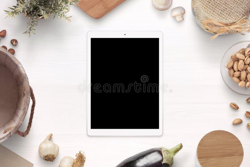 Tableta con la maqueta de la pantalla en blanco en la tabla de madera blanca rodeada con los artículos y los ingredientes viejos  imagen de archivo libre de regalías