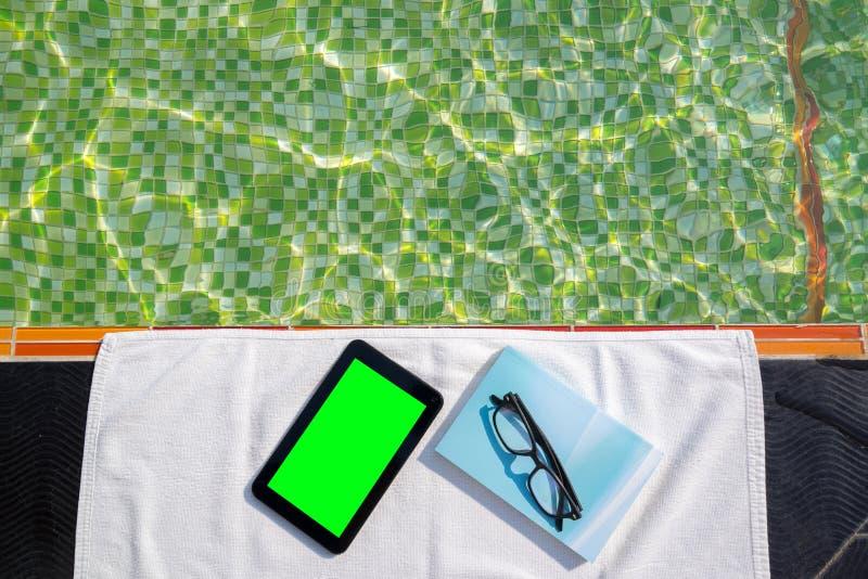 Tableta con la pantalla en blanco y el libro azul con los vidrios que mienten en la toalla blanca en el poolside imágenes de archivo libres de regalías