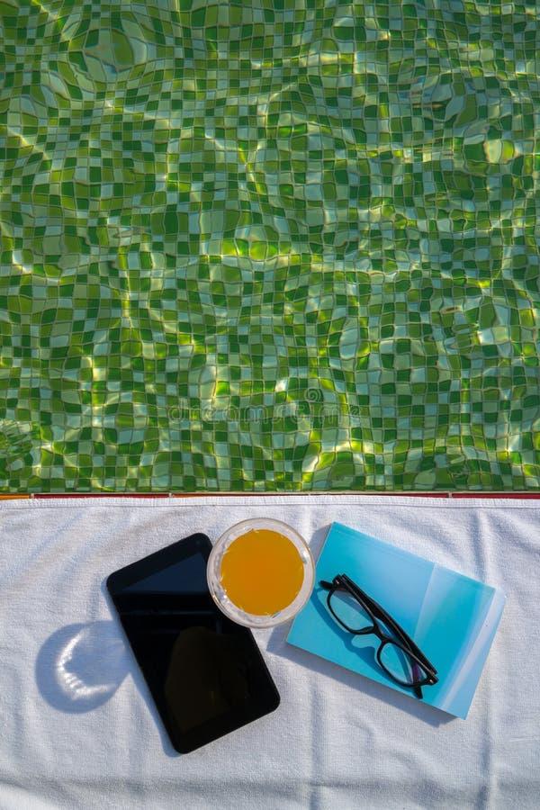 Tableta con la pantalla vacía, un vidrio de zumo de naranja y el libro azul con los vidrios en la toalla blanca imagen de archivo
