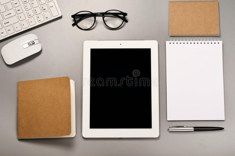 Tableta con un teclado, un ratón, vidrios, una pluma y una libreta imagen de archivo libre de regalías