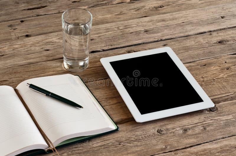 Tableta con una pantalla en blanco en una tabla de madera imagenes de archivo