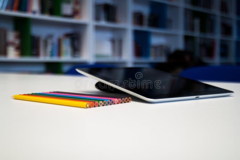 Tableta con una pantalla en blanco y creyones coloridos en el tabl del escritorio foto de archivo