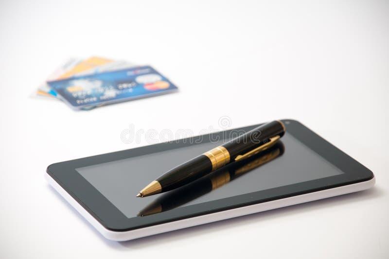 Tableta con una pluma negra y tarjetas de crédito en el fondo foto de archivo