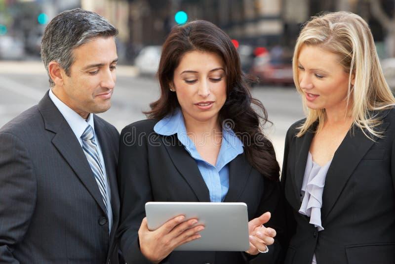 Tableta de And Businesswomen Using Digital del hombre de negocios afuera foto de archivo libre de regalías
