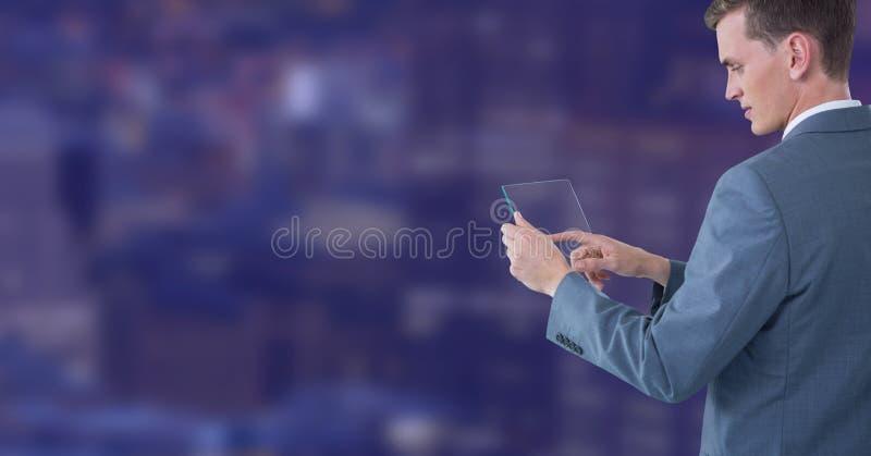 Tableta de cristal conmovedora del hombre de negocios contra ciudad de la noche imagenes de archivo