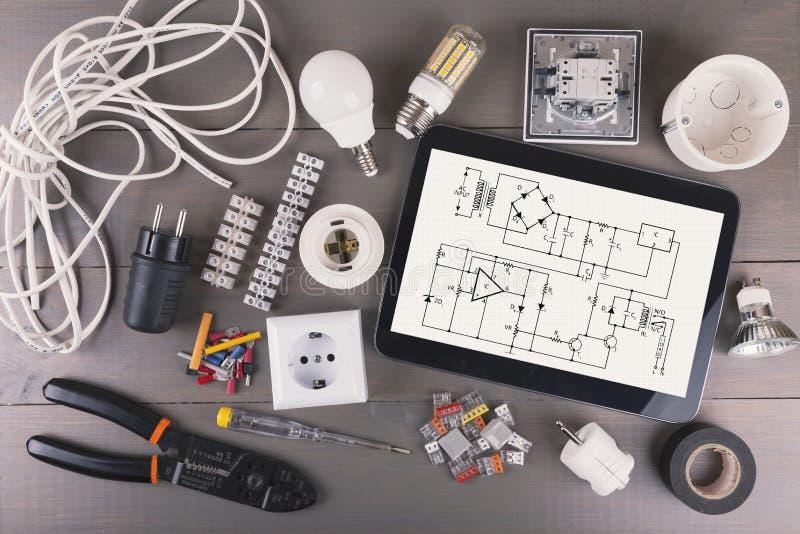 Tableta de Digitaces con esquema del circuito y el equipo eléctrico imágenes de archivo libres de regalías