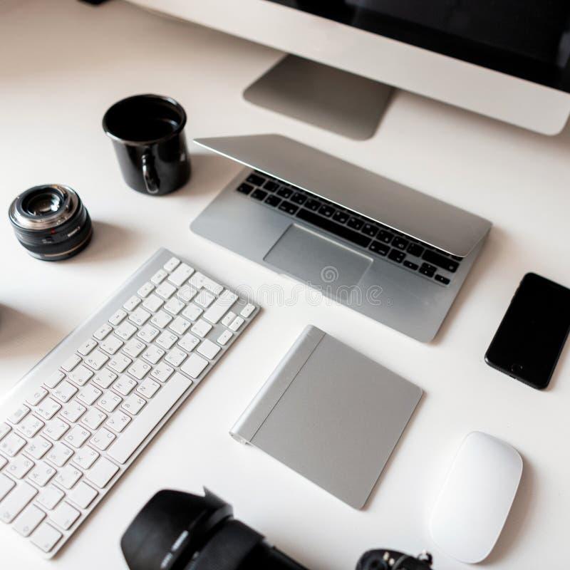 Tableta de gráficos, cámara, ordenador portátil, taza negra, objetos, teclado, teléfono móvil y ratón inalámbrico en una tabla de imagen de archivo libre de regalías