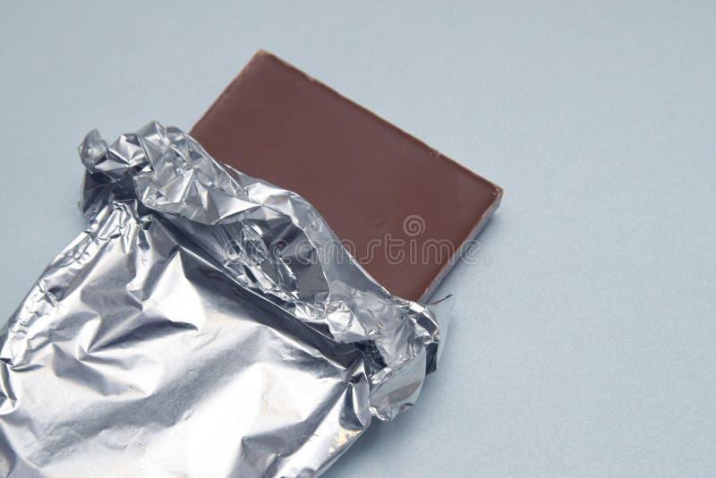 Tableta de la barra de chocolate envuelta en papel de aluminio sobre Gray Neutral Background con el espacio de la copia Invitació fotos de archivo libres de regalías