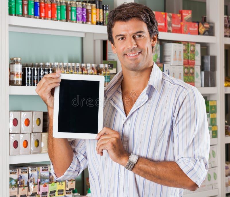 Tableta de la demostración del hombre en colmado imagen de archivo libre de regalías