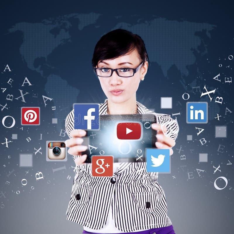 Tableta de la demostración del trabajador con el icono social de la red imagenes de archivo