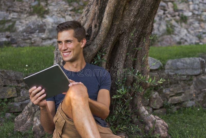 Tableta de la lectura del hombre y disfrutar de resto en un parque debajo de ?rbol imagen de archivo
