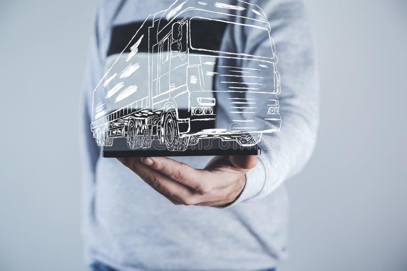 Tableta de la mano del hombre con el camión imagen de archivo
