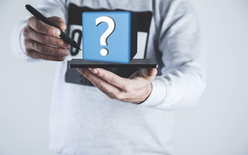 Tableta de la mano del hombre con el signo de interrogación fotografía de archivo