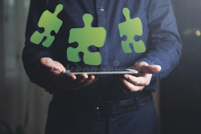 Tableta de la mano del hombre con rompecabezas fotos de archivo