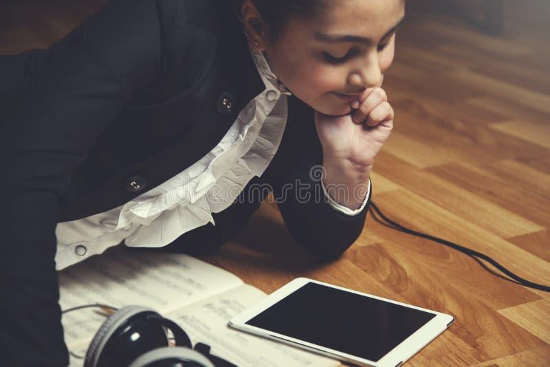 Tableta de la mano de la muchacha con el libro de música imagen de archivo libre de regalías