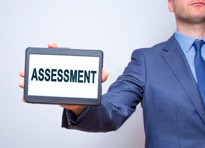 Tableta de la tenencia de la mano del hombre de negocios con la muestra del texto de la evaluación isola fotos de archivo