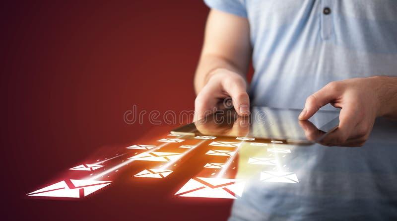 Tableta de la tenencia de la mano y envío de iconos del correo electrónico imagenes de archivo