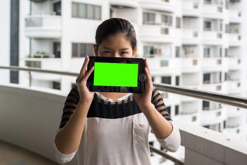 Tableta de la tenencia de la mujer en su pantalla del verde del espacio en blanco del handswith fotos de archivo libres de regalías