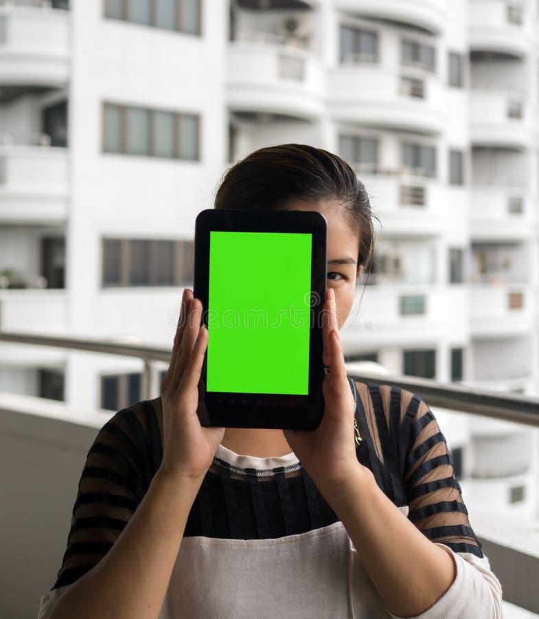 Tableta de la tenencia de la mujer en sus manos con la pantalla verde en blanco foto de archivo
