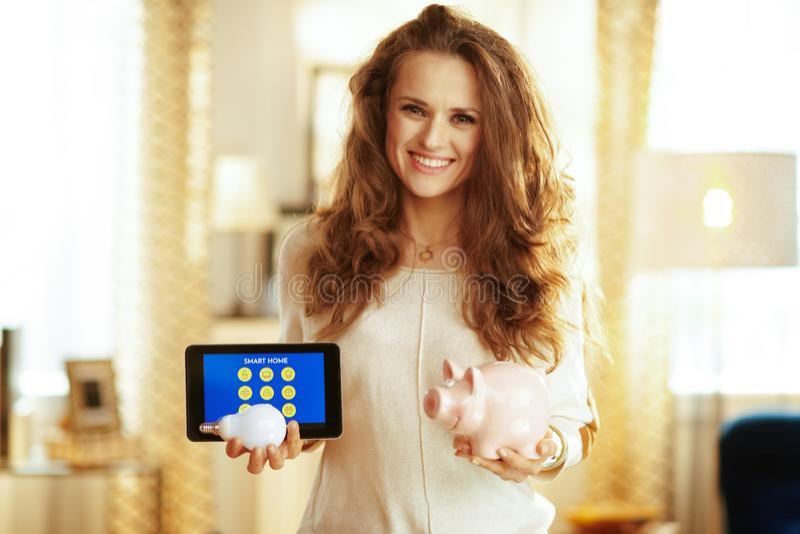 Tableta de la tenencia del ama de casa con el app casero elegante, lámpara elegante y fotos de archivo libres de regalías