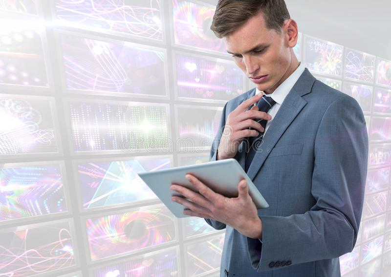 Tableta de la tenencia del hombre de negocios con representaciones visuales coloridas brillantes de las pantallas foto de archivo libre de regalías
