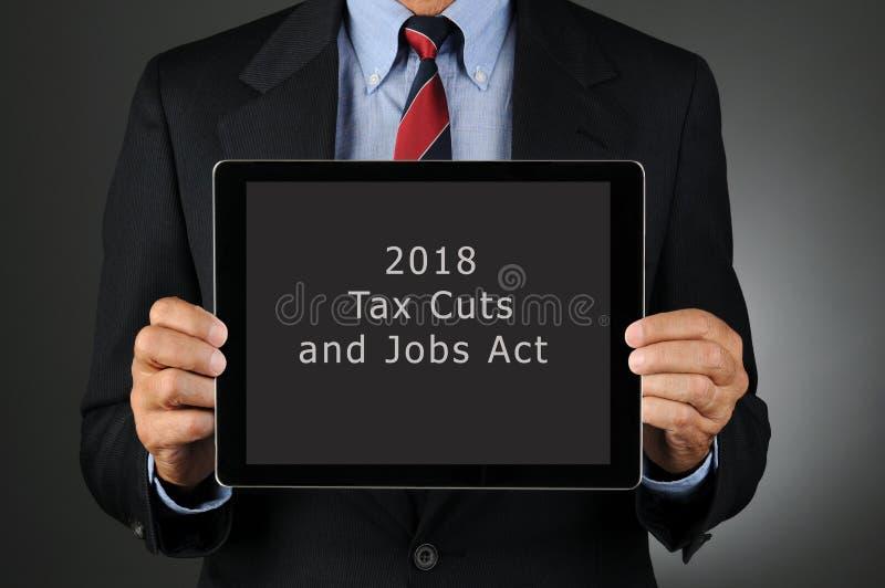 Tableta de la tenencia del hombre de negocios con 2018 reducciones de impuestos y acto de los trabajos foto de archivo libre de regalías