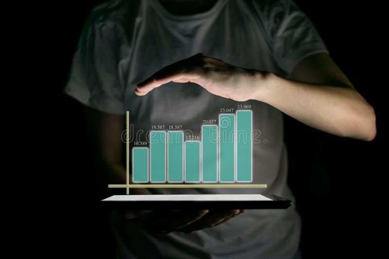 Tableta de la tenencia del hombre de negocios y mostrar un holograma virtual cada vez mayor de estadísticas fotografía de archivo libre de regalías