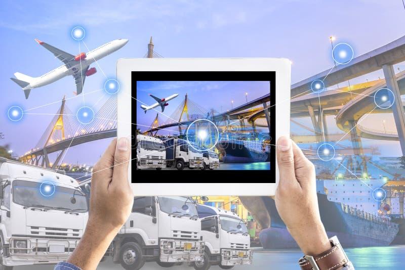 Tableta de la tenencia de la mano con el interfaz de la pantalla en la logística delantera industrial imágenes de archivo libres de regalías
