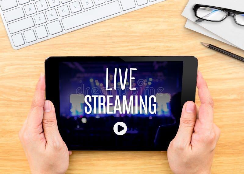 Tableta de la tenencia de la mano con la palabra de Live Streaming en la tabla de madera, Inte imagen de archivo