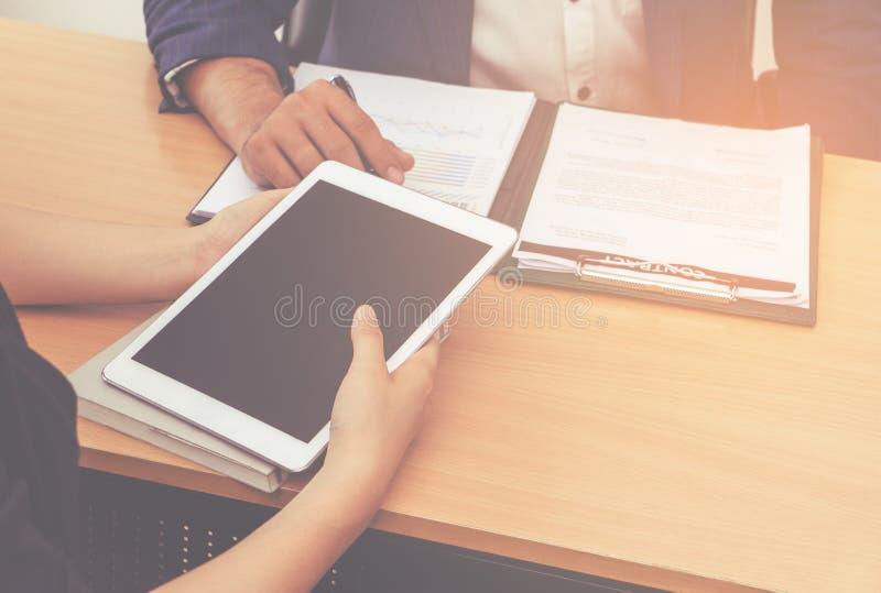 Tableta de la tenencia de la mujer de negocios en la reunión del socio imagen de archivo libre de regalías