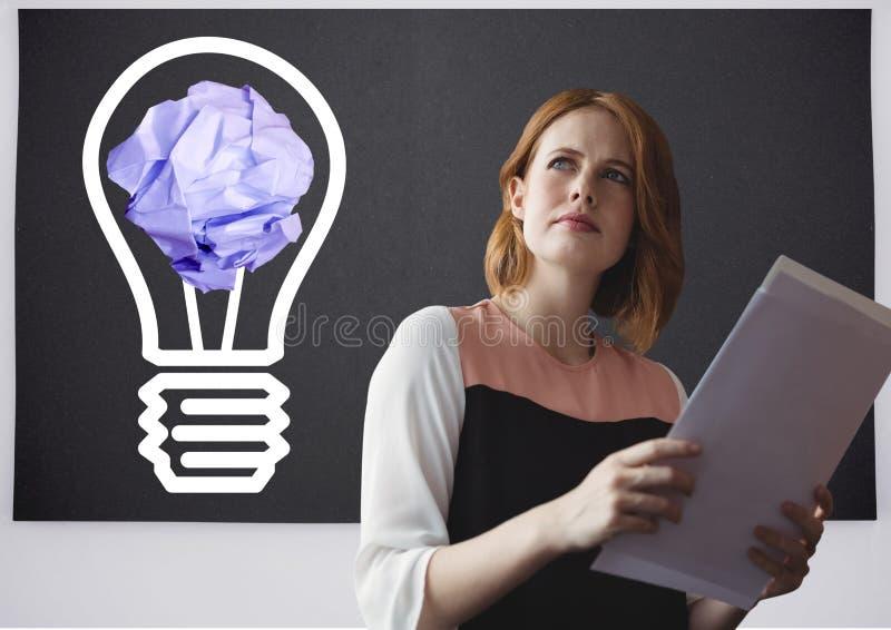Tableta de la tenencia de la mujer que se coloca al lado de bombilla con la bola de papel arrugada delante de la pizarra imagen de archivo