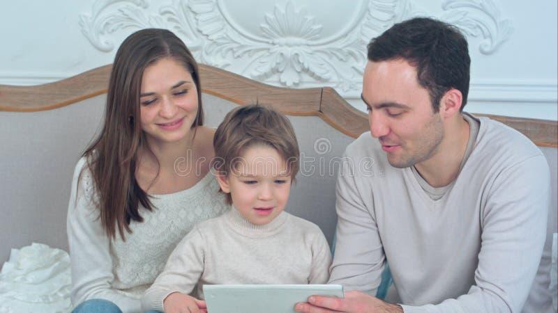 Tableta de observación feliz de la familia y del hijo en el sofá imagen de archivo libre de regalías