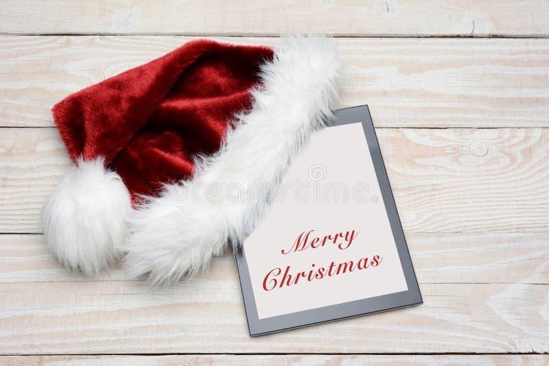 Tableta de Santa Hat With Happy Holidays imagenes de archivo