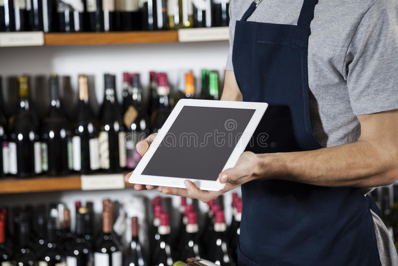 Tableta de Showing Blank Digital del vendedor en tienda de vino fotografía de archivo