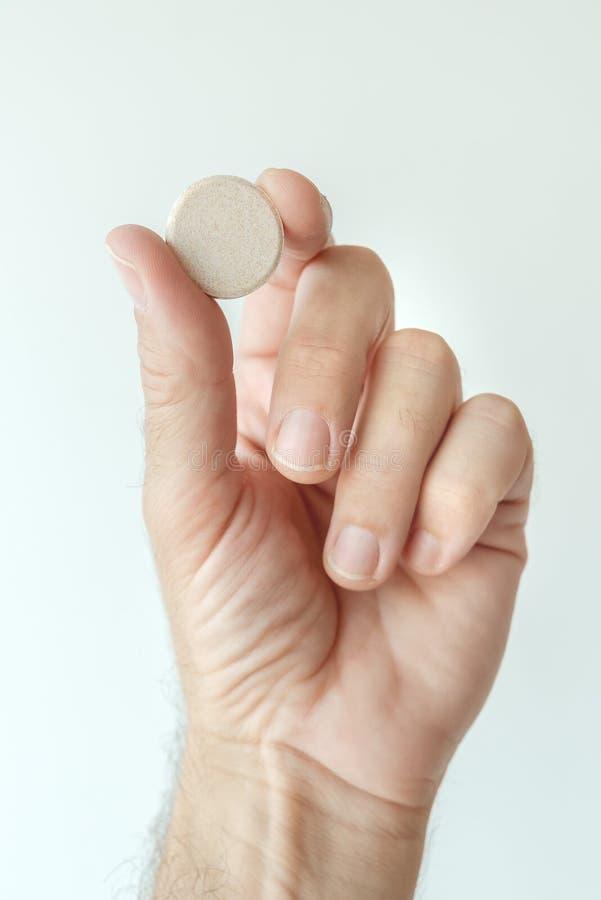 Tableta de vitamina efervescente en la mano masculina fotos de archivo libres de regalías