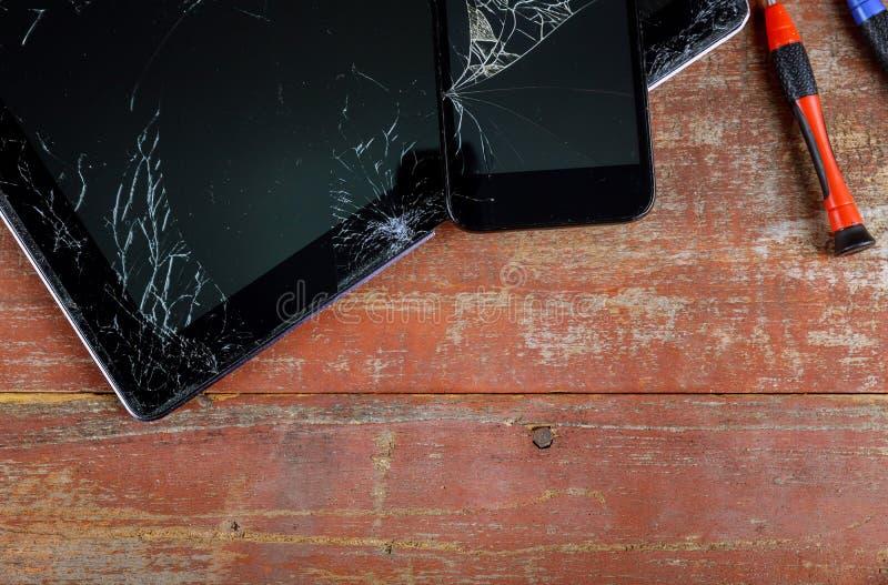 Tableta del ordenador de la reparación y teléfono elegante con la pantalla táctil quebrada en el escritorio de madera foto de archivo