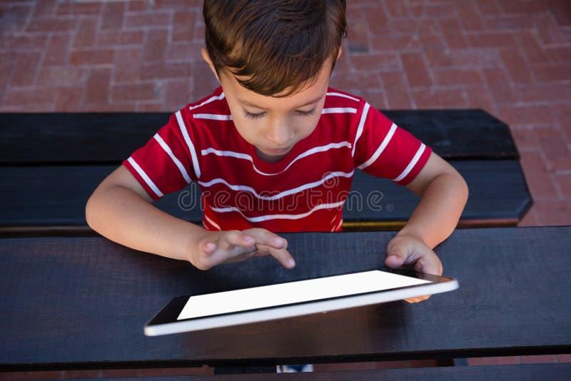 Tableta digital conmovedora del muchacho mientras que se sienta en la tabla en escuela fotografía de archivo