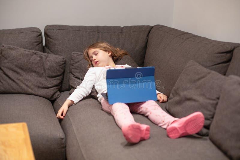 Tableta digital de observación el dormir de la niña que miente en couc fotos de archivo