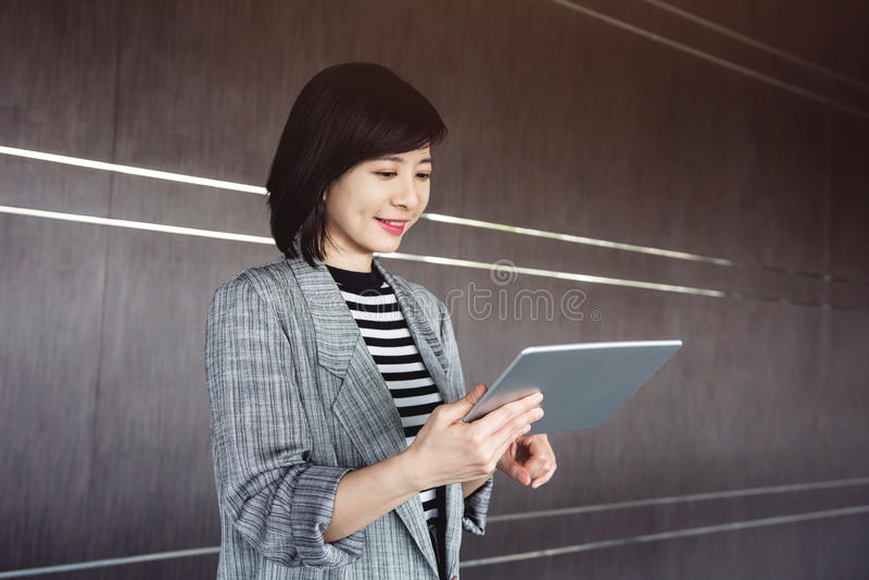 Tableta digital del uso atractivo y confiado de la trabajadora dentro fotos de archivo libres de regalías