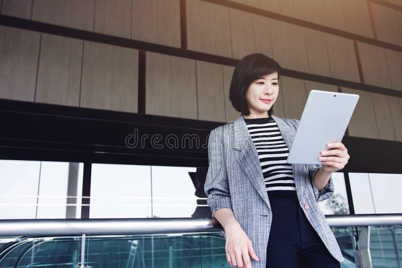 Tableta digital del uso atractivo y confiado de la trabajadora dentro fotos de archivo