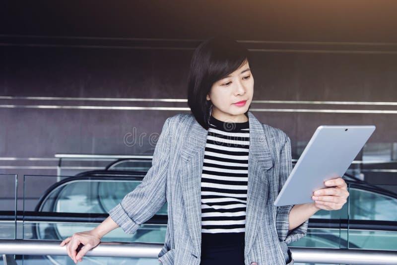 Tableta digital del uso atractivo y confiado de la trabajadora dentro foto de archivo libre de regalías