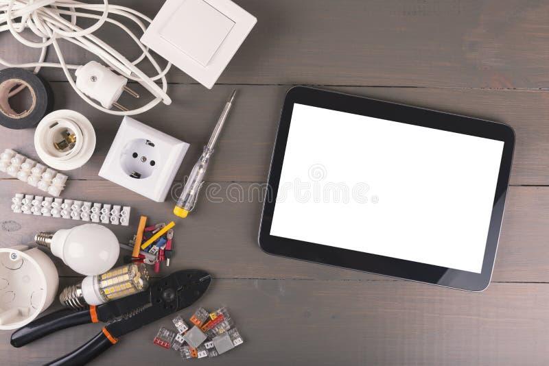 Tableta digital en blanco con las herramientas y los accesorios eléctricos en la tabla de madera fotografía de archivo