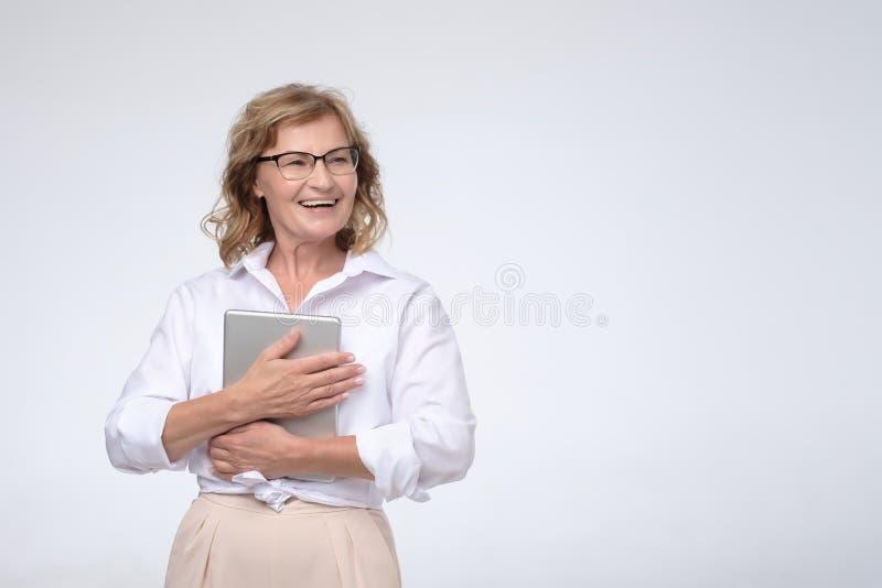 Tableta digital que se considera amistosa encantada sonriente de la mujer madura caucásica magnífica, mirando a un lado foto de archivo libre de regalías