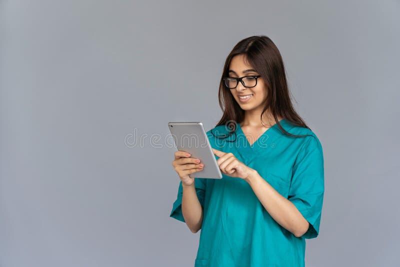 Tableta digital sonriente de la mujer del uso indio joven de la enfermera aislada en fondo gris fotografía de archivo