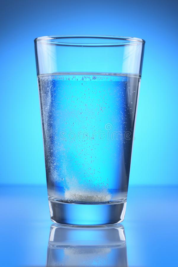 Tableta efervescente en el vidrio de agua fotos de archivo libres de regalías